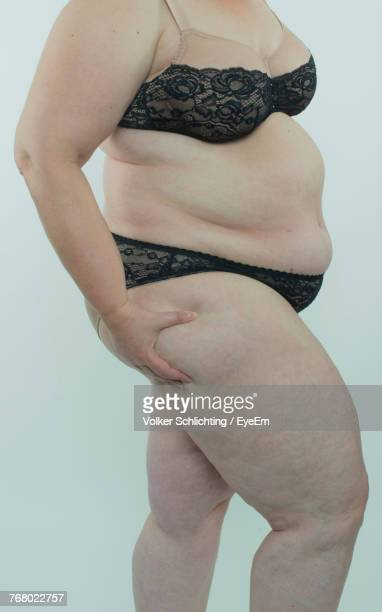 close-up of overweight woman holding thigh against white background - chubby legs stock photos and pictures