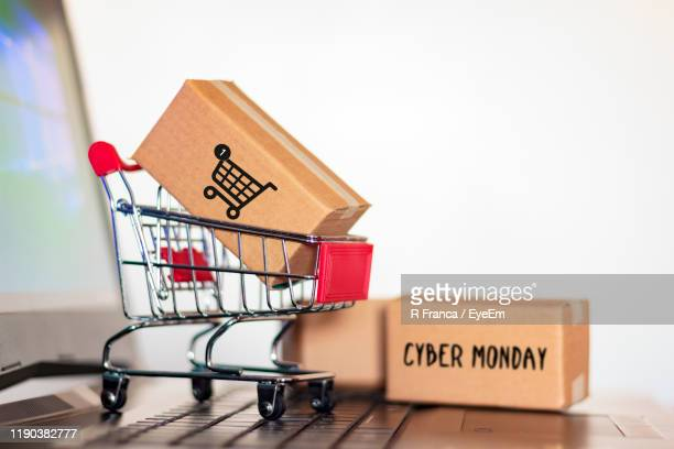 close-up of package in small shopping cart on laptop against white background - cyber monday stock pictures, royalty-free photos & images