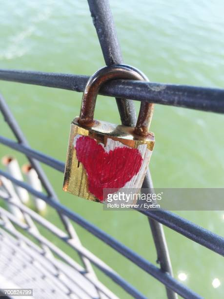 Close-Up Of Padlock Attached On Fence Over Lake