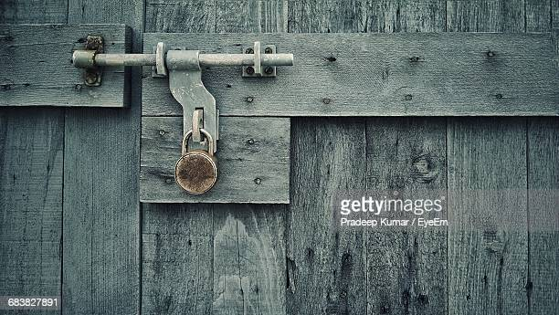 Close-Up Of Padlock Attached To Wooden Door