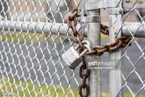 close-up of padlock on chainlink fence - prison stock pictures, royalty-free photos & images