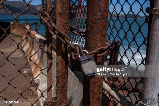 close-up of padlock on rusty chainlink fence at promenade - oleksandr vakulin stock pictures, royalty-free photos & images