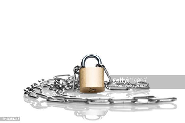Close-Up Of Padlock With Chain Over White Background