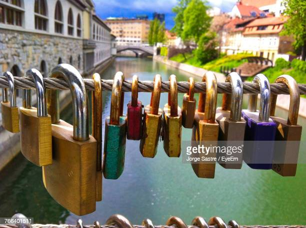 Close-Up Of Padlocks Hanging On Railing Against Canal