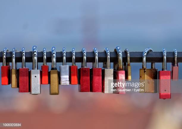 close-up of padlocks hanging on railing against sky - padlock stock photos and pictures