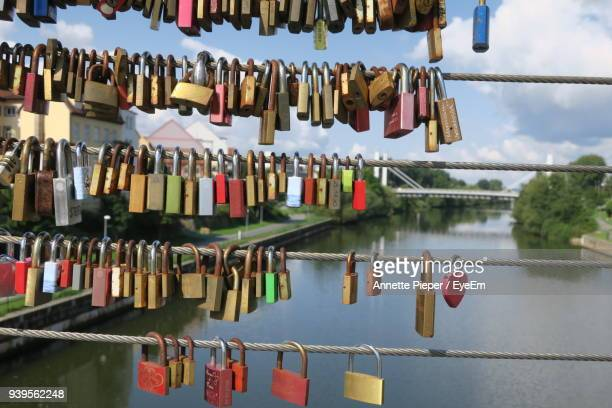 close-up of padlocks hanging on railing against sky - annette haven foto e immagini stock
