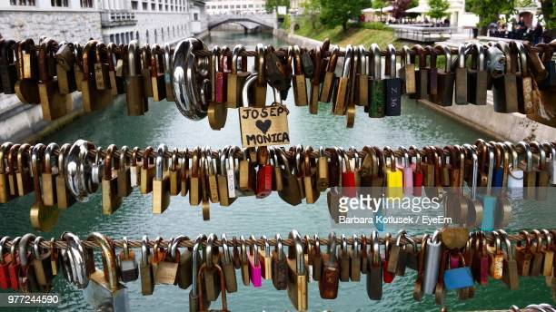 Close-Up Of Padlocks Hanging On Railing Over Canal In City