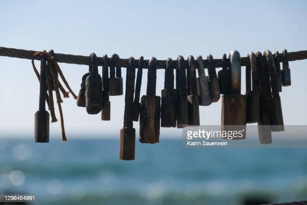 close-up of padlocks on rope against sky - アルブフェイラ ストックフォトと画像