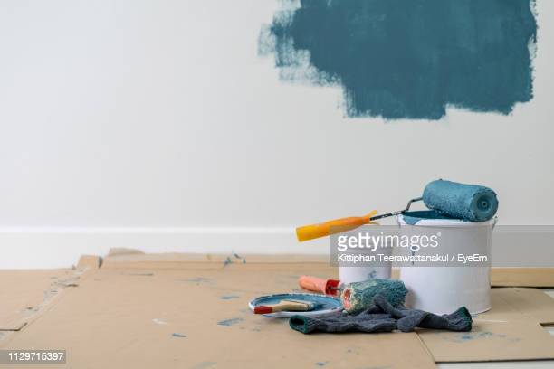 close-up of paint roller on container against wall - home improvement stock pictures, royalty-free photos & images
