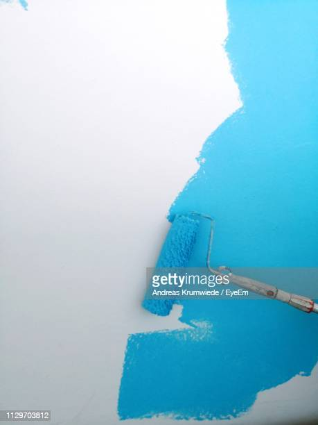Close-Up Of Paint Roller On Wall