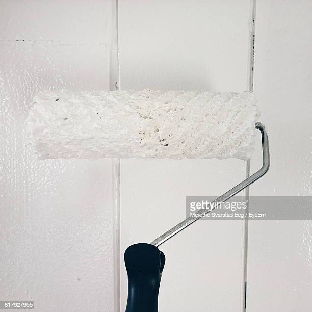 Close-Up Of Paint Roller On White Wall