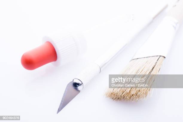 Close-Up Of Paintbrush With Knife And Dropper Over White Background