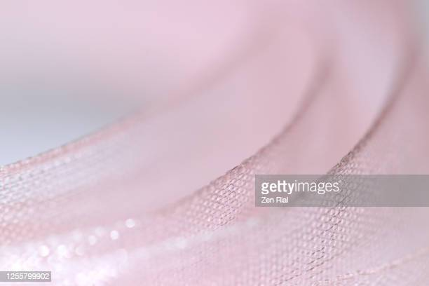 close-up of pale pink textured ribbons in a row showing edges - チュール生地 ストックフォトと画像