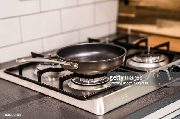 close-up of pan on stove at home - saucepan stock pictures, royalty-free photos & images