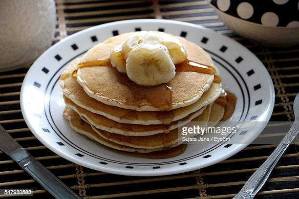 Close-Up Of Pancakes With Banana In Plate On Table