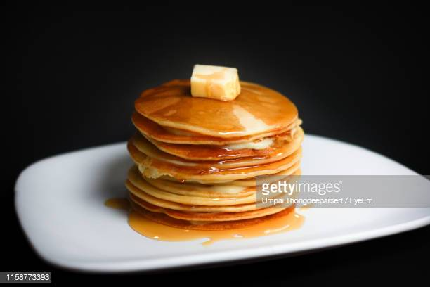 close-up of pancakes with butter in plate against black background - pancake stock pictures, royalty-free photos & images