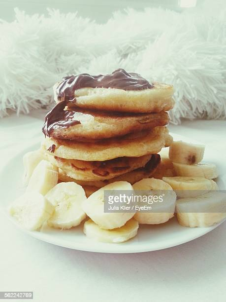 Close-Up Of Pancakes With Chocolate Sauce And Sliced Banana Served On Bed