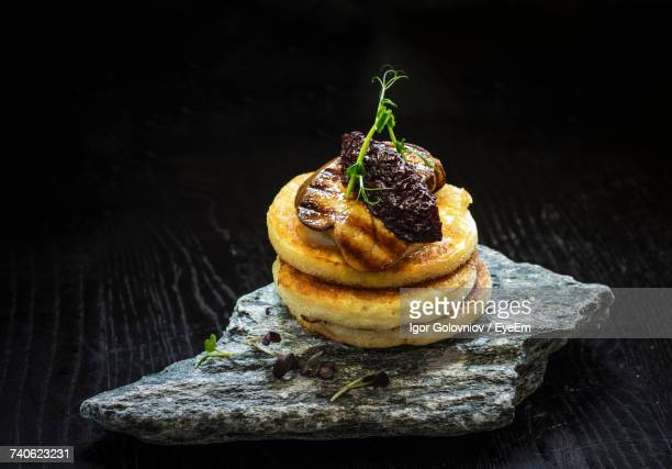 Close-Up Of Pancakes With Fried Foie Gras And Onion Marmalade On Stone At Table