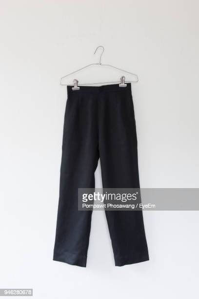 close-up of pants on coathanger on white background - black trousers stock pictures, royalty-free photos & images