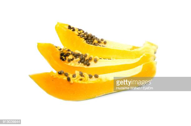 Close-Up Of Papaya With Seeds Against White Background