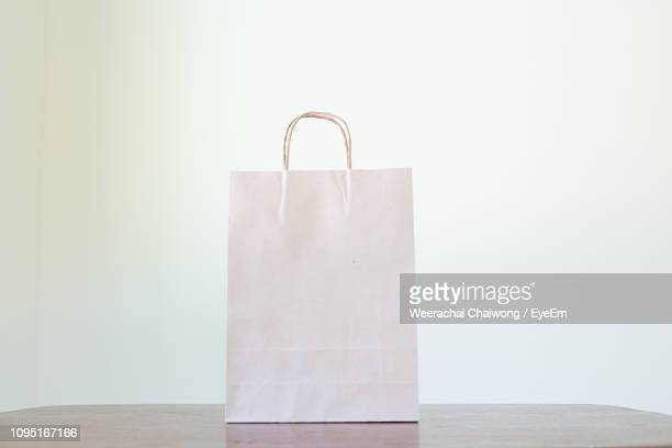 close-up of paper bag on table against white wall - 紙袋 ストックフォトと画像