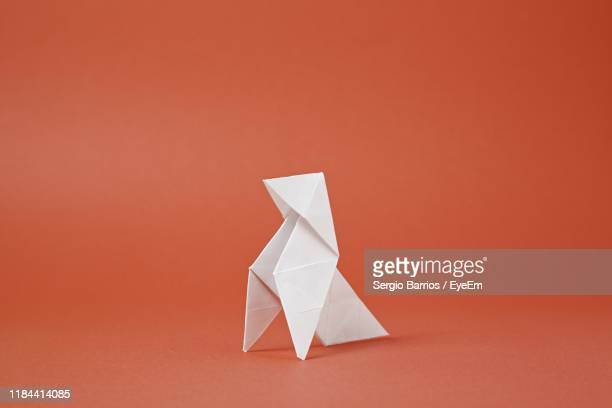 close-up of paper bird against red background - origami photos et images de collection