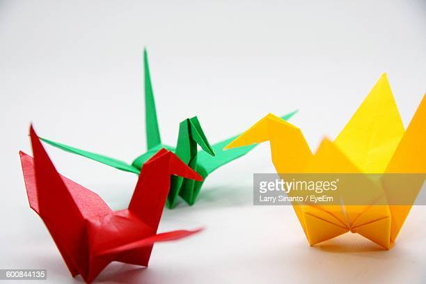Close-Up Of Paper Cranes Against White Background