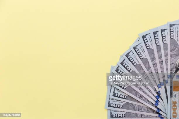 close-up of paper currencies on yellow background - american one hundred dollar bill stock pictures, royalty-free photos & images