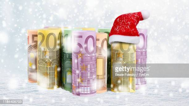 close-up of paper currencies with santa hat on table during snowfall - christmas cash stock pictures, royalty-free photos & images