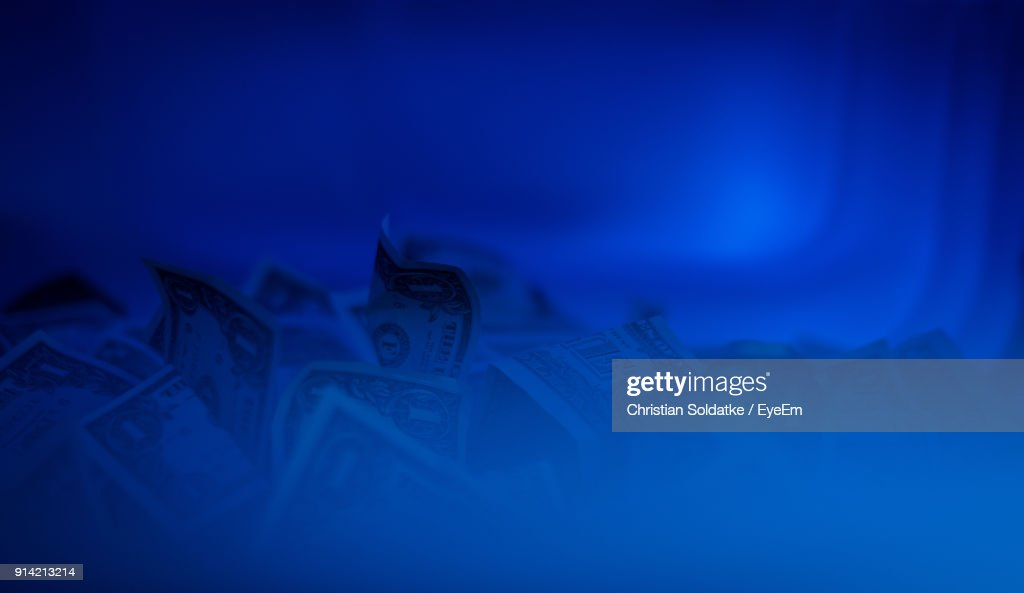 Close-Up Of Paper Currency Amidst Blue Smoke : Stockfoto