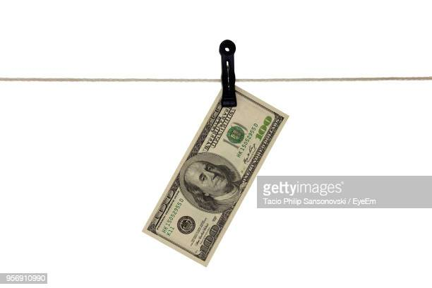close-up of paper currency hanging on clothesline against white background - représentation humaine photos et images de collection