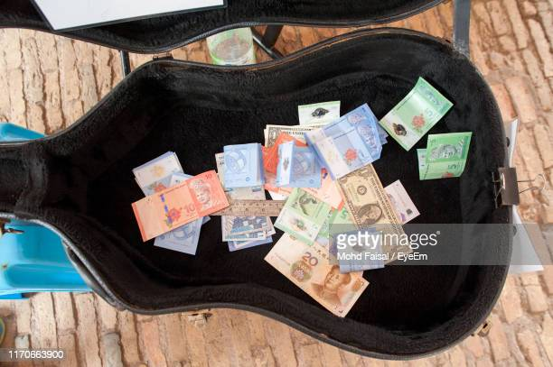 close-up of paper currency in guitar case on table - guitar case stock pictures, royalty-free photos & images