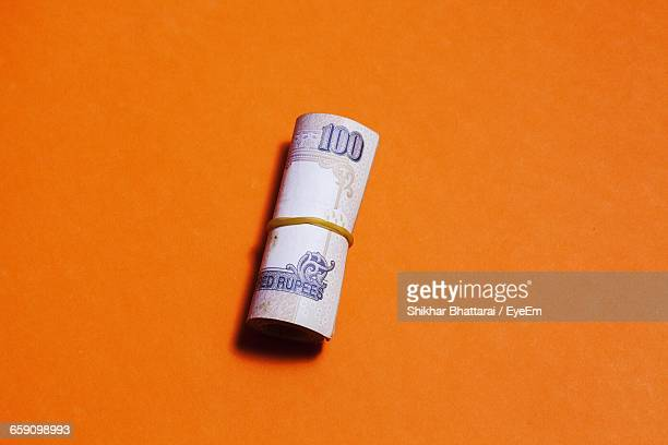 Close-Up Of Paper Currency On Orange Table