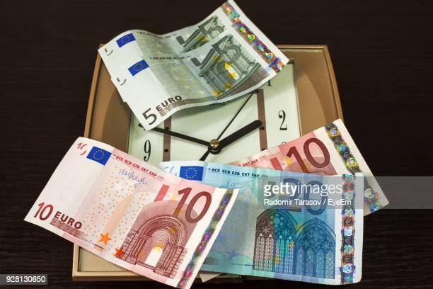 close-up of paper currency with clock on table - twenty euro banknote stock photos and pictures