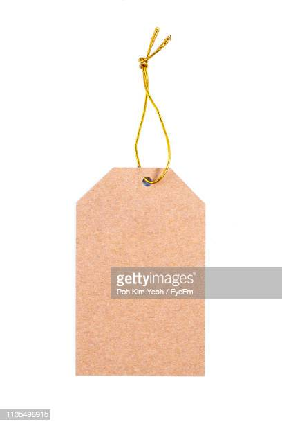 close-up of paper hanging against white background - price tag stock pictures, royalty-free photos & images