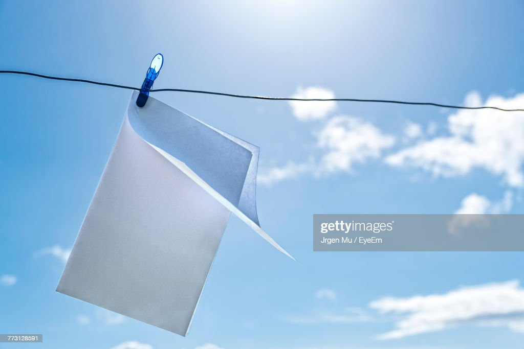 Close-Up Of Paper Hanging From Clothespin On String Against Blue Sky : Photo