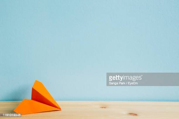 close-up of paper plane on table against blue wall - paper airplane stock pictures, royalty-free photos & images