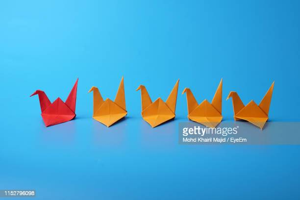 close-up of paper swans on blue background - five objects stock pictures, royalty-free photos & images