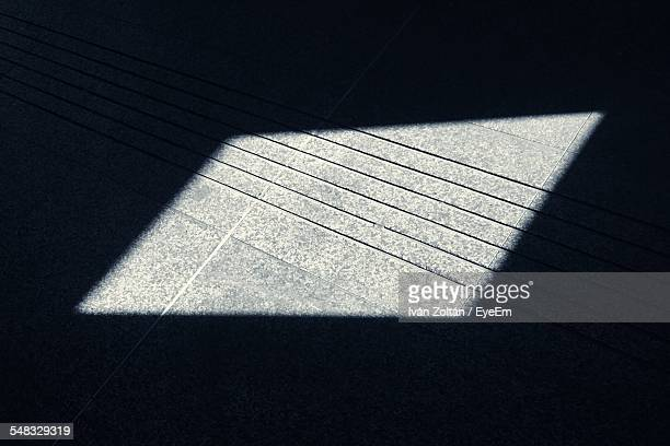 Close-Up Of Parallelogram Shape Sunlight On Floor In Dark Room