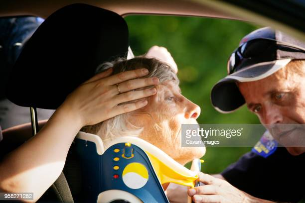 Close-up of paramedic putting neck brace on patient in car