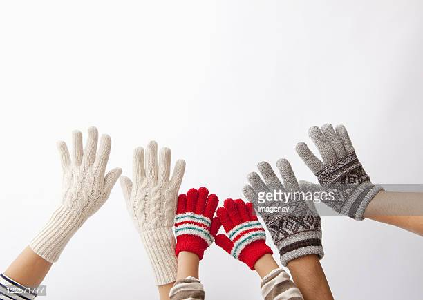 Closeup of parents and child's hands wearing gloves