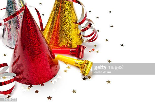 Close-up of party hats, whistles, streamers, confetti isolated on white