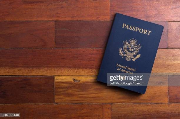 close-up of passport on wooden table - passeport photos et images de collection