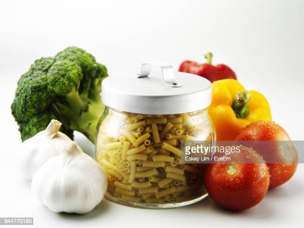 close-up of pasta in jar with vegetables and garlic over white background - yellow bell pepper stock pictures, royalty-free photos & images