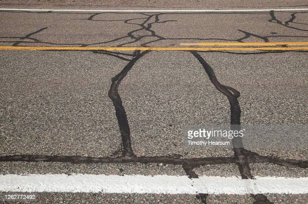 close-up of patched route 66 road surface with yellow center stripes and white side markings - timothy hearsum stockfoto's en -beelden