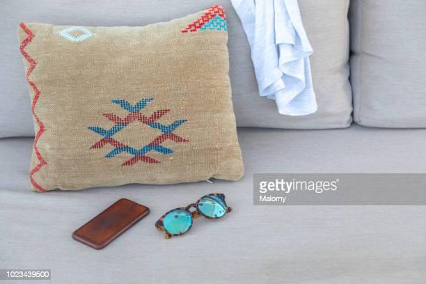 close-up of patterned pillow, smartphone, shirt and sunglasses on sofa. marrakesh, marrakesh-safi, morocco. - nordafrika stock-fotos und bilder