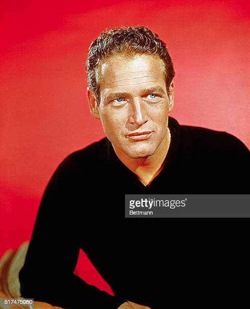 Close-up of Paul Newman wearing a black sweater. Red background.