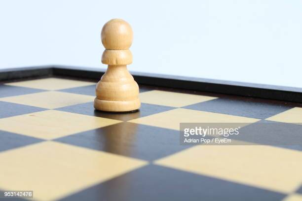 Close-Up Of Pawn On Chess Board Against White Background