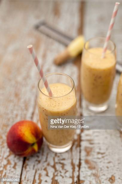 Close-Up Of Peach And Banana Smoothie On Wooden Table