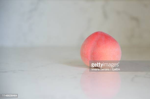close-up of peach on table - peach stock pictures, royalty-free photos & images